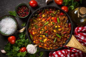 Chili con carne in skillet on dark stone table.
